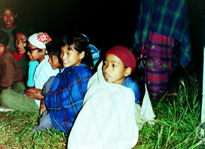 Village children watching their friends perform.