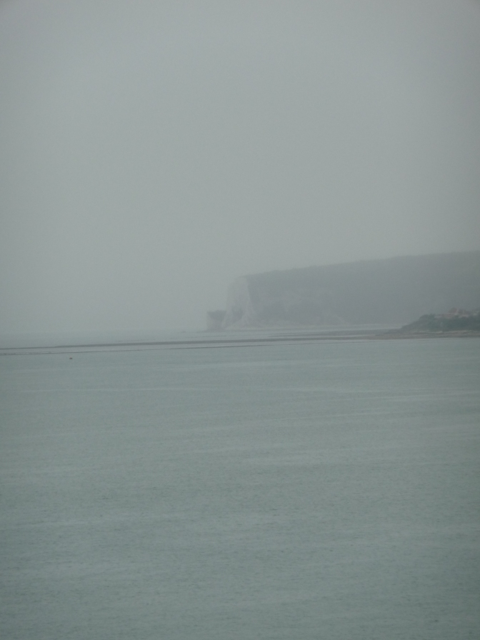 Lost in the mists of the still foggy morning, the great cliffs slowly disappear.