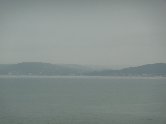 To the left of the port town, the hills disappear into the morning mists.