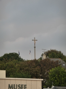 Raised atop the ridge to commemorate the fallen, the cross towers over Arromanche.