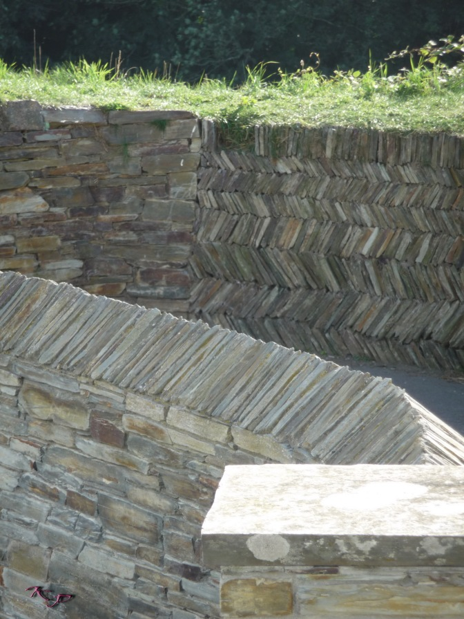 Like the ocean waves, the walls zig and zag along the village lane.