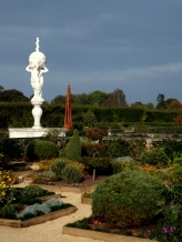 The early Autumn garden is muted, like old tapestry colours. Still, the statue calls her on.