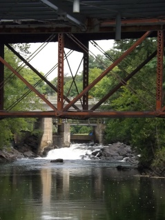 The support beams for the railway bridge in Bracebridge are juxtapositioned in front of the falls at the Bird Mill Pumping Station on the Muskoka River.