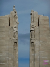 Justice, Hope, Charity, Faith, Truth, Knowledge and Peace, reaching a torch high, crown the monument.
