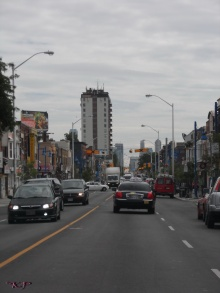 On Bloor Street eastbound in Toronto a lone vehicle crosses the traffic near Dufferin.