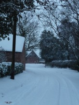 Under its blanket of snow, the village lies hushed.