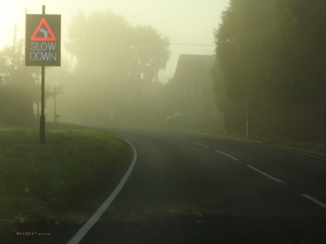 A road sign warns drivers to be careful going around the misty morning curve.