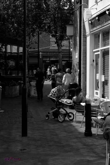 Mother and child having lunch, stroller momentarily abandoned.